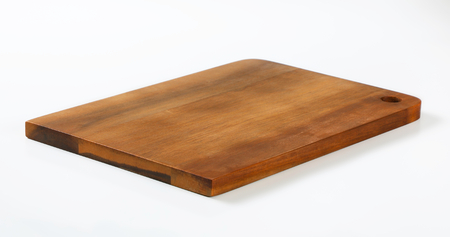 wooden cutting board with hole on white background