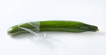 single long cucumber unwrapped and unpeeled on white background