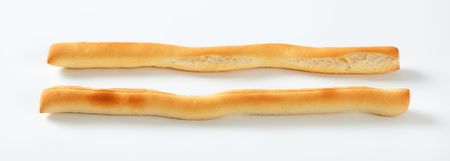 two crispy bread sticks on white background
