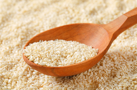 spoon of healthy sesame seeds on sesame seeds background - detail