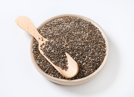 bowl of healthy chia seeds and wooden scoop on white background Reklamní fotografie