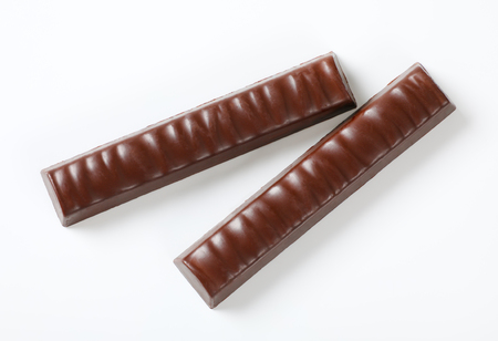 two unwrapped chocolate sticks with filling on white background