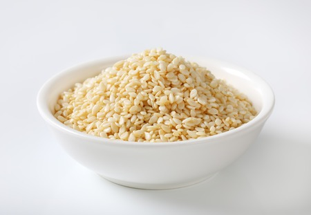 bowl of healthy sesame seeds on white background