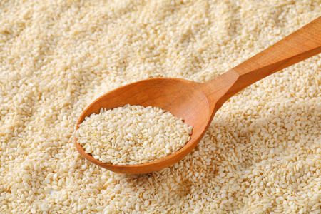 spoon of healthy sesame seeds on sesame seeds background