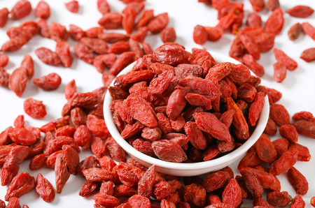 bowl and pile of healthy goji berries on white background