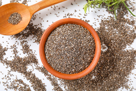 bowl of healthy chia seeds and wooden spoon on white background