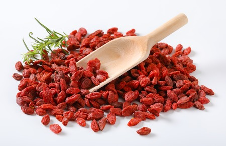 pile of healthy goji berries and woooden scoop on white background Reklamní fotografie