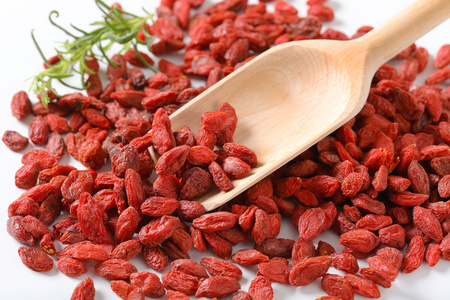 pile of healthy goji berries and woooden scoop - close up