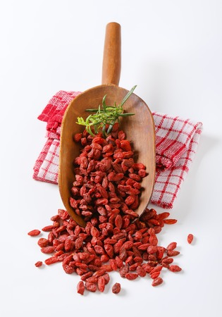 scoop of healthy goji berries and rosemary twigs on checkered dishtowel