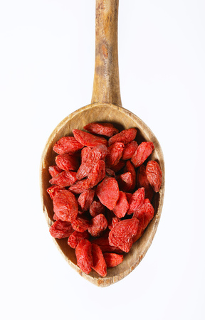 spoon of healthy goji berries on white background