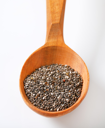 spoon of healthy chia seeds on white background