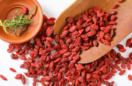 scoop of healthy goji berries and bowl of rosemary twigs on white background