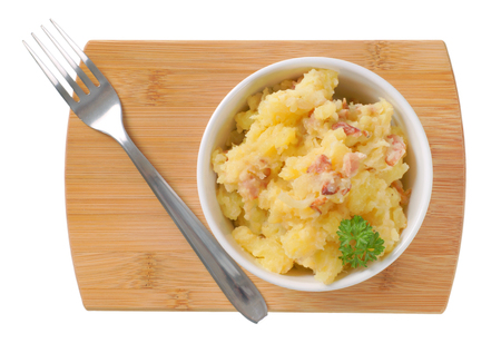 bowl of crushed potatoes with bacon on wooden cutting board
