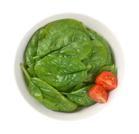 bowl of fresh spinach leaves on white background