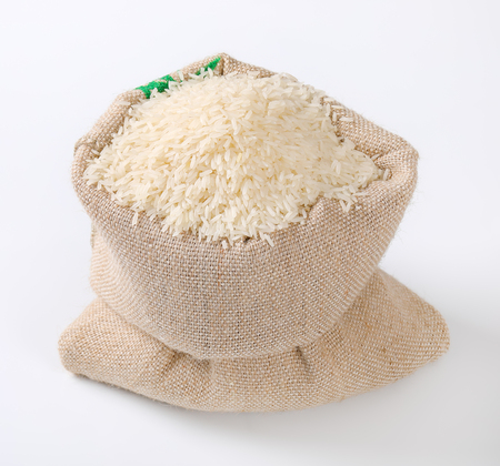 bag full of white long grained rice on white background