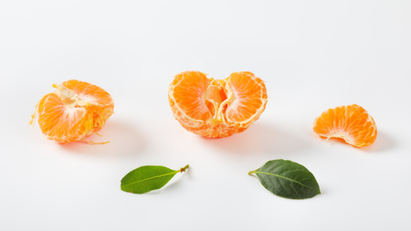 ripe peeled tangerine and leaves on white background