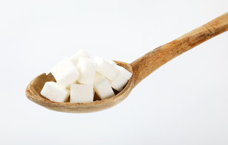 spoon of white sugar cubes on white background