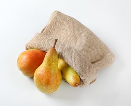 ripe pears in burlap sack on white background Reklamní fotografie - 106000231