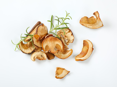handful of dried mushrooms and fresh rosemary on white background