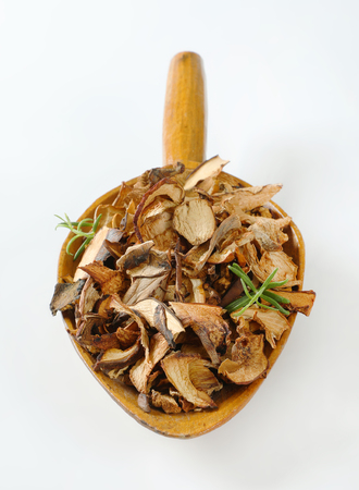 scoop of dried mushrooms on white background