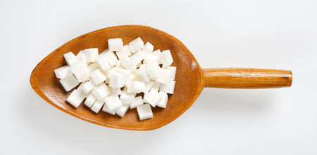 scoop of white sugar cubes on white background Reklamní fotografie