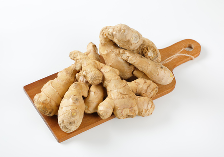 fresh ginger roots on wooden cutting board