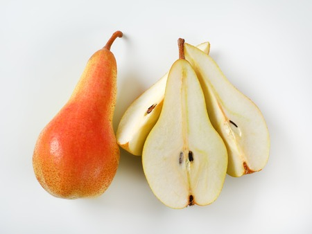 whole and sliced yellow pears on white background