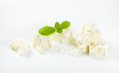 pieces of crumbly white cheese on white background Reklamní fotografie - 106000061