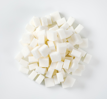 pile of white sugar cubes on white background