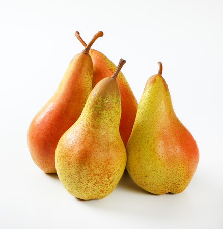 four ripe pears on white background