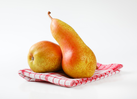 two ripe pears on checkered dishtowel