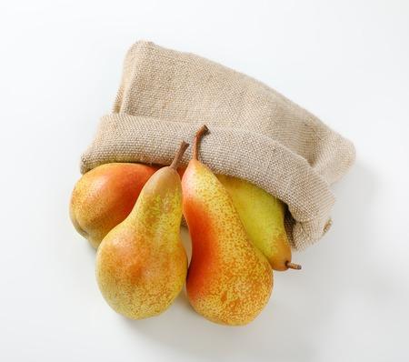 ripe pears in burlap sack on white background Reklamní fotografie