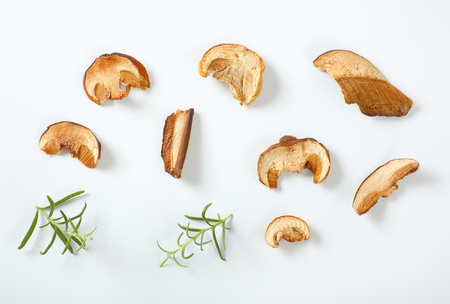 slices of dried mushrooms and rosemary on white background Reklamní fotografie
