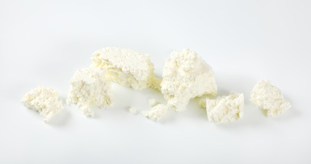 pieces of crumbly white cheese on white background
