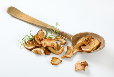 handful of dried mushrooms and long wooden spoon on white background Reklamní fotografie