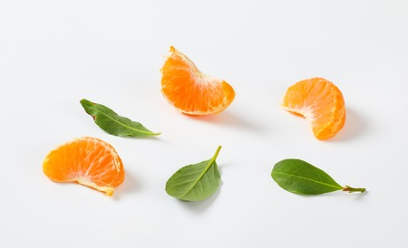 segments and leaves of ripe tangerine on white background