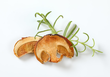 slices of dried mushrooms and fresh rosemary on white background
