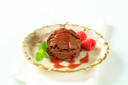 Scoop of chocolate ice cream with toffee sauce and raspberries