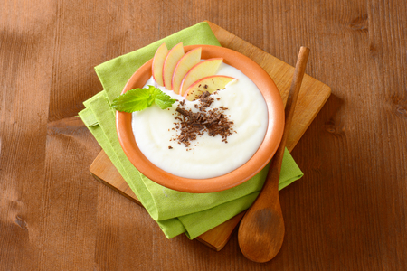 Bowl of milk pudding with apple slices and grated chocolate