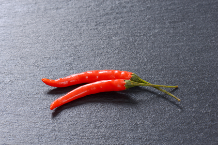 Two red hot chilli peppers on black background