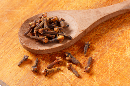Dried cloves on wooden spoon