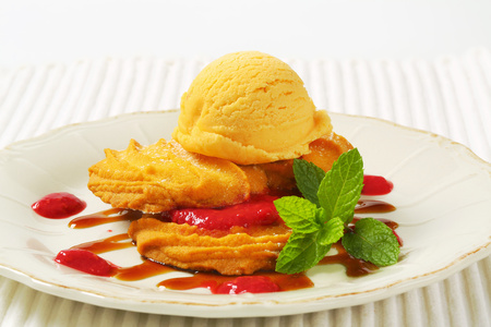 Spritz butter cookies with raspberry sauce and scoop of yellow ice cream Reklamní fotografie - 115160176