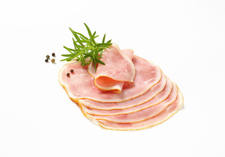 Thin slices of cooked ham on white background