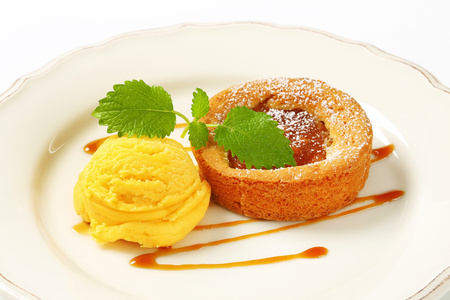 Small apple filled tart and scoop of yellow ice cream Reklamní fotografie - 115160216