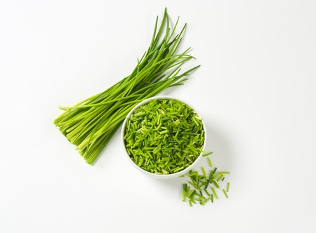 Bowl of fresh chopped chives and bundle of chives next to it