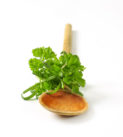 Fresh parsley and rosemary on wooden spoon