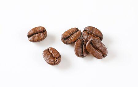 Roasted coffee beans on white background Фото со стока