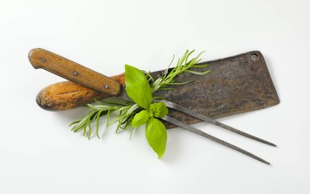 Old meat cleaver knife, carving fork and fresh culinary herbs