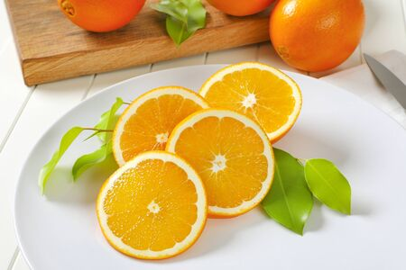 Fresh oranges slices on white plate
