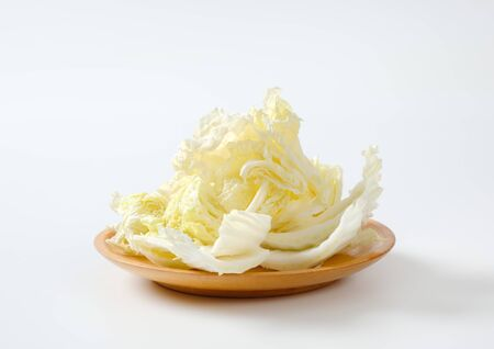 Fresh Chinese cabbage leaves on wooden plate